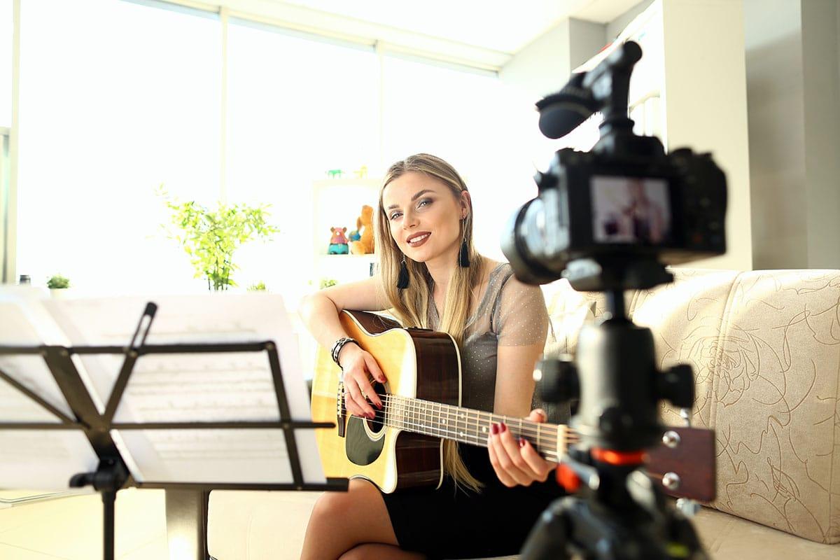 Digitale Bühne - gewinnt an Bedeutung - Frau mit Gitarre am streamen - Blog - Beitragsbild