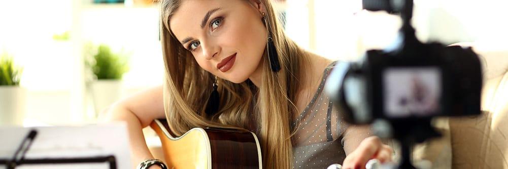 Digitale Bühne - gewinnt an - Musikerin mit Gitarre am streamen - Blog - Titlebild